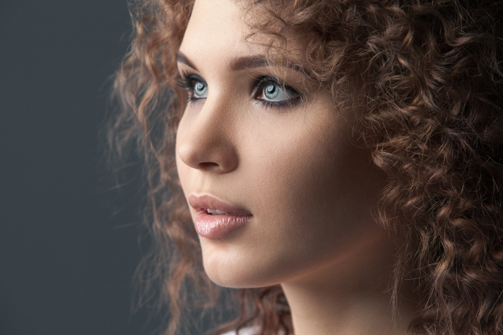 Close up portrait of beautiful woman face on gray background